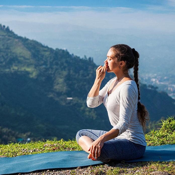 Woman practices pranayama in lotus pose outdoors